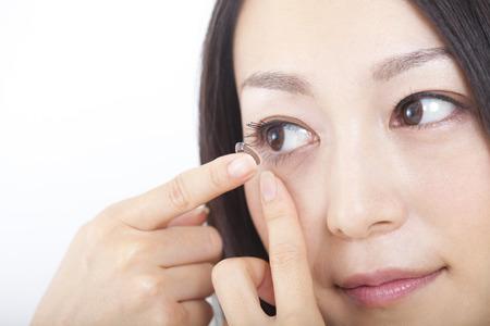 Foto de Women put a contact lens in the eye - Imagen libre de derechos