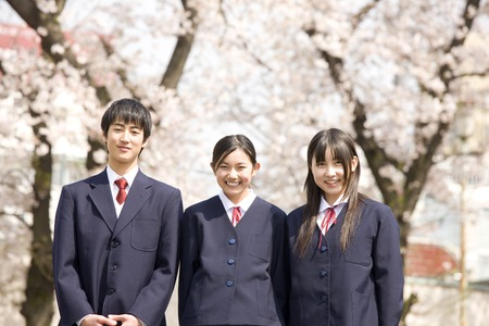 Junior high school students men and women are laughing under the cherry tree