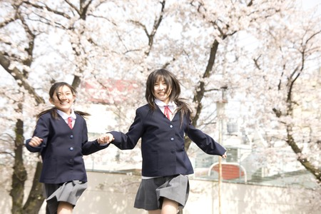 Two middle school girls of running hand in hand