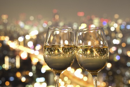 Photo pour Night view of the city reflected in the glass of wine - image libre de droit