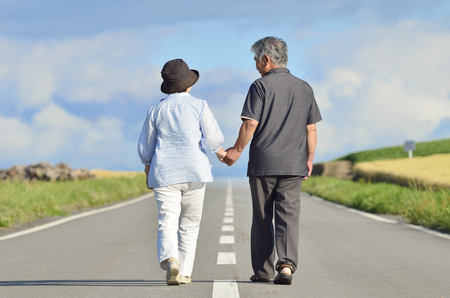 Foto per Senior couple walking a single road holding hands - Immagine Royalty Free