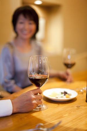 Foto de Men and women enjoy a conversation while drinking wine - Imagen libre de derechos