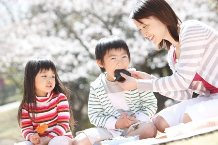 Mothers feed rice balls to children