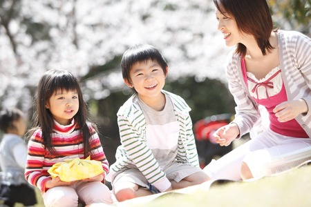 Mother to pass a lunch to children under the cherry tree