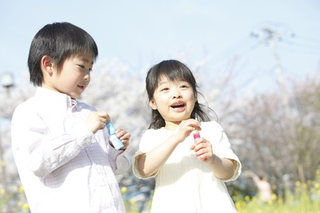 Elementary school students men and women playing with soap bubble