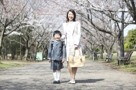 Elementary school boys and mother standing under the cherry trees