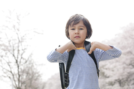 Boy standing by carrying a school bag