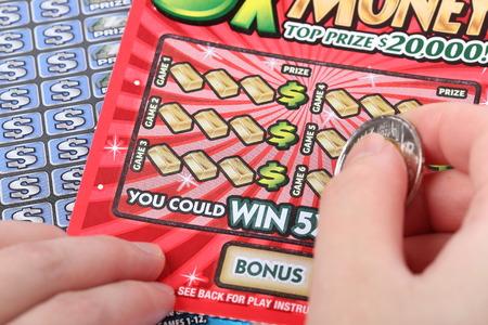 Foto de A human hand is scratching a lottery ticket - Imagen libre de derechos