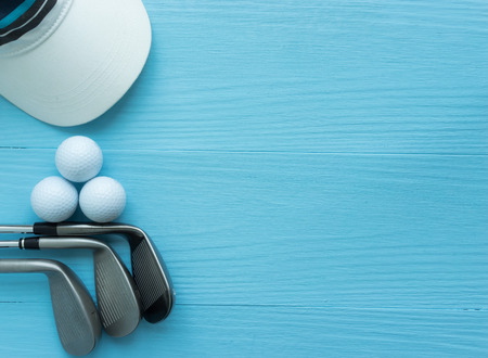 Photo for Golf clubs, golf balls, cap, on blue wooden table, with copy space. - Royalty Free Image