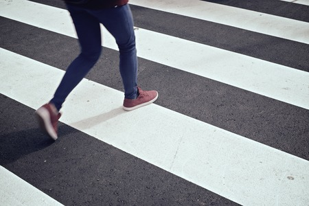 Photo for Young woman crossing a zebra crossing. - Royalty Free Image