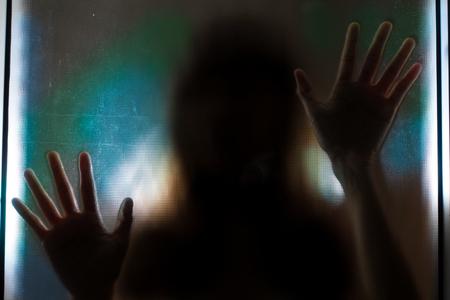 Photo pour Woman shadow behind translucent glass. - image libre de droit