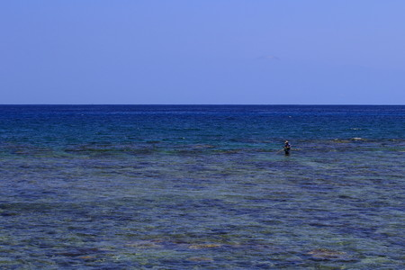 Photo for Lone fly fisherman in a wide blue bay in landscape format with copy space - Royalty Free Image