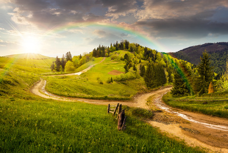 Foto de composite autumn landscape. fence near the cross road on hillside meadow in mountains. few fir trees of forest  on both sides of the road in sunset light with rainbow - Imagen libre de derechos