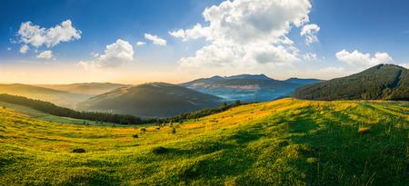 Foto de agricultural field on hillside in mountains near village in morning light - Imagen libre de derechos