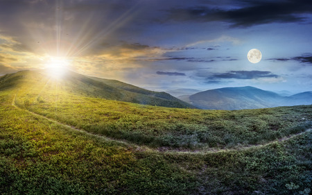 Photo pour day and night concept image with path through a large meadow on the hillside in high mountains - image libre de droit