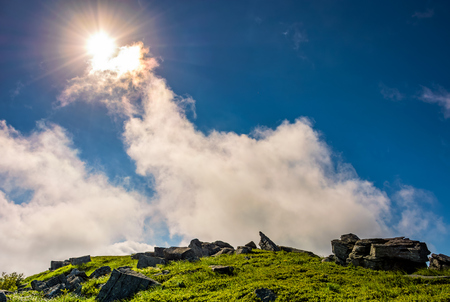 Photo for sunburst on a blue sky with clouds over the mountains with rocky hillside - Royalty Free Image