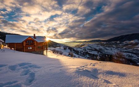 Photo pour wooden chalet in village outskirts at sunrise. gorgeous landscape in winter Carpathian mountains, great place for vacation - image libre de droit