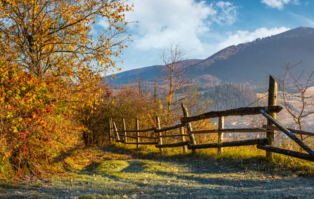Photo pour autumn rural scenery with fence on hillside. yellow foliage on trees and mountain ridge in a distance under the blue sky - image libre de droit