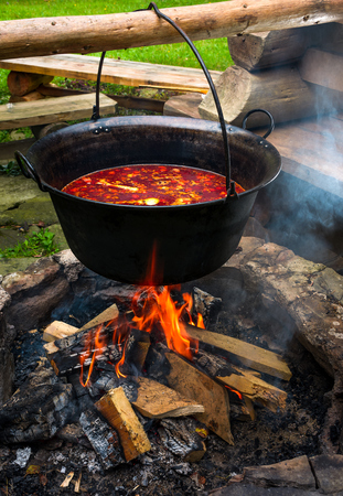 Foto de traditional Hungarian Goulash soup in cauldron. meal cooked outdoors on an open fire. delicious and healthy food popular in Central Europe - Imagen libre de derechos