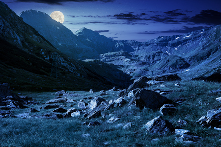 Photo pour lovely scenery of Transfagarasan road in valley at night in full moon light. rocks on grassy meadow and slopes. half of the valley in shade of mountain ridge - image libre de droit