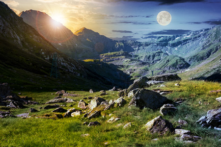 Foto de time change concept in Transfagarasan valley. rocks on grassy meadow and slopes lit by sun and moon simultaneously. half of the valley in shade of mountain ridge - Imagen libre de derechos
