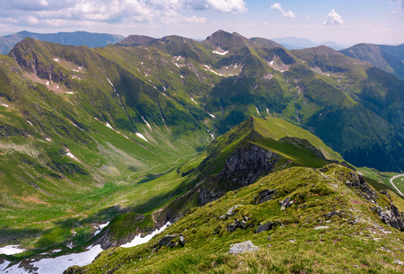 Photo pour ridge with grassy slopes and cliffs. Southern Carpathian mountains in a far distance. beautiful summer scenery of Romania - image libre de droit