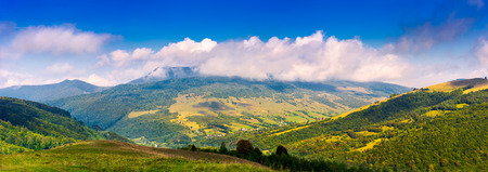 Photo pour panorama of mountainous rural area in autumn. lovely countryside scenery with fluffy clouds above the ridge - image libre de droit