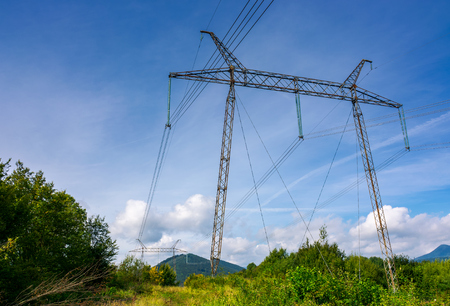 Foto de power line tower on a hillside. giant metal construction in beautiful landscape. power and energy concept - Imagen libre de derechos