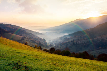 Photo for rainbow above the village in foggy valley. beautiful mountainous countryside at sunrise in autumn - Royalty Free Image