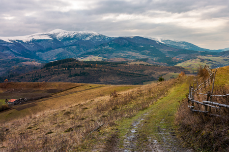 Foto de Rural area in november. wooden fence by the country road. mighty ridge with snowy peaks in the distance. gloomy autumn weather - Imagen libre de derechos