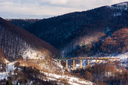 Photo for winter rail road transportation in mountains. freight train with colorful carriage on the old viaduct - Royalty Free Image