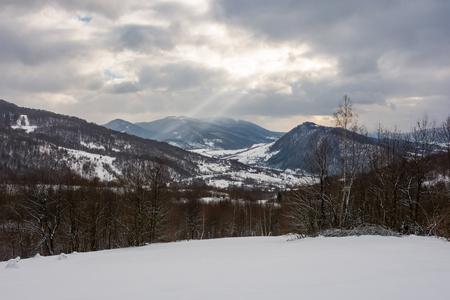 Foto per gloomy winter day in mountains. dark forest behind the snowy meadow. beam of light from grey cloudy sky fall into the distant valley - Immagine Royalty Free