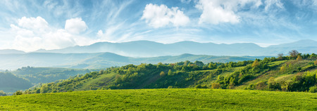Foto de panorama of beautiful countryside of romania. sunny afternoon. wonderful springtime landscape in mountains. grassy field and rolling hills. rural scenery - Imagen libre de derechos