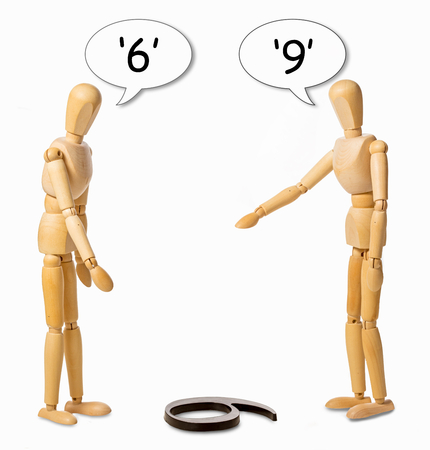 Photo pour two mannikins arguing whether a number on the floor is a 6 or a 9 - image libre de droit