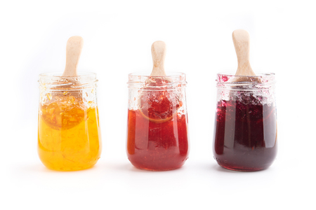 Foto de Open jar of strawberry, orange and blueberries  jam and a spoon, isolated on white - Imagen libre de derechos