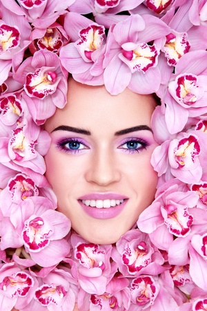 Portrait of young beautiful smiling woman with stylish make-up and pink orchids around her face