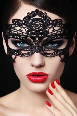 Photo pour Portrait of young beautiful blue-eyed woman in black lacy mask - image libre de droit
