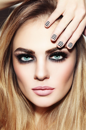 Foto de Portrait of young beautiful sexy girl with smoky eyes and stylish striped manicure - Imagen libre de derechos