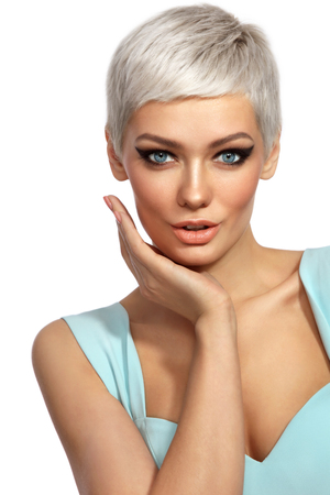 Photo pour Young beautiful tanned woman with stylish cat eye make-up and platinum blonde hair touching her face over white background, copy space - image libre de droit