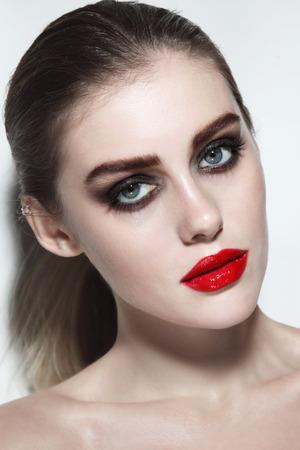 Foto de Young beautiful woman with red lipstick and smoky eye make-up - Imagen libre de derechos