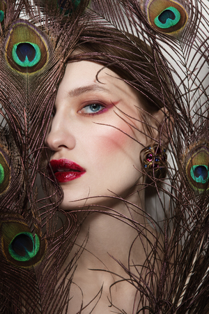 Foto de Glamorous portrait of young beautiful woman in peacock feathers - Imagen libre de derechos