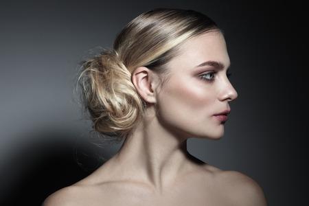 Foto de Profile portrait of young beautiful woman with fancy messy hair bun - Imagen libre de derechos
