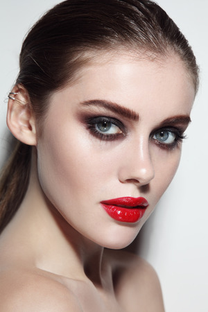 Foto de Young beautiful girl with smoky eye makeup and red lips - Imagen libre de derechos
