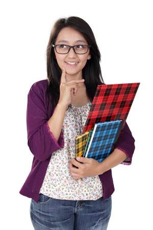 Photo pour Friendly Asian teacher holding some books and looking to her side imaginatively, isolated on white background - image libre de droit