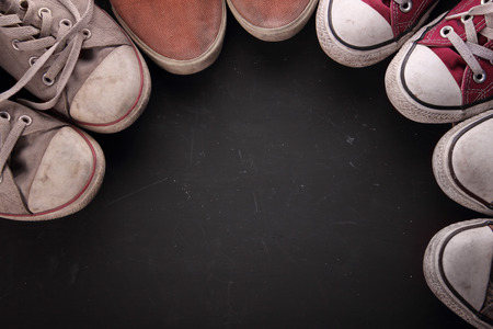 Photo pour Overhead shot of some dirty sneakers' tips making a circle for copy space on black textured background - image libre de droit