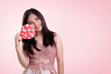 Photo pour Adorable Asian teenage girl holding a heart shaped box on her cheek, looking up imaginatively to copy space on light pink background - image libre de droit