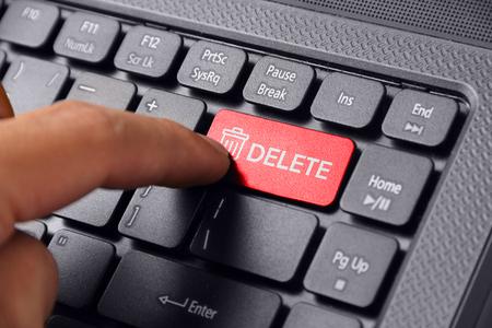Foto de Gesture of a hand finger pressing DELETE on a laptop keyboard - Imagen libre de derechos
