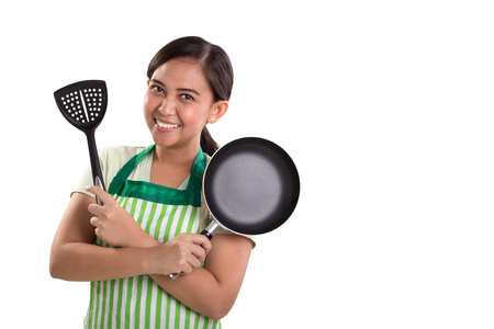 Foto per Beautiful Asian woman holding cooking utensils with arms crossed pose, isolated on white background for copy space - Immagine Royalty Free
