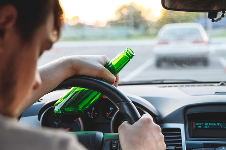 Photo pour Drunk young man driving a car with a bottle of beer. Dont drink and drive concept. Driving under the influence. DUI, Driving while intoxicated. DWI - image libre de droit