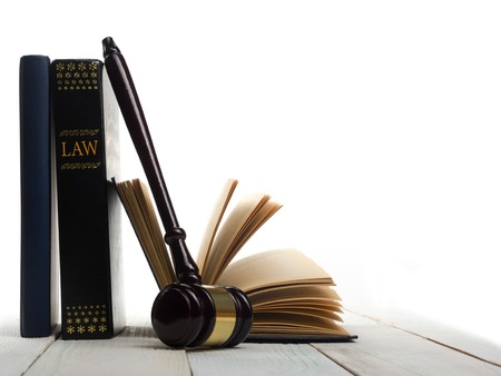 Foto de Law concept - Open law book with a wooden judges gavel on table in a courtroom or law enforcement office isolated on white background. Copy space for text. - Imagen libre de derechos